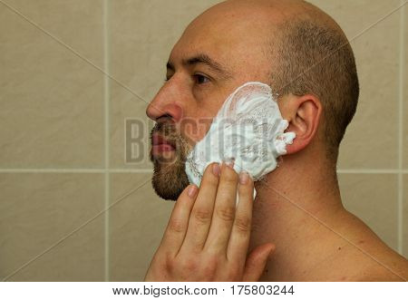 Portrait of a good looking young man putting shaving cream on his face and ready to shave his beard in the bathroom. Bald