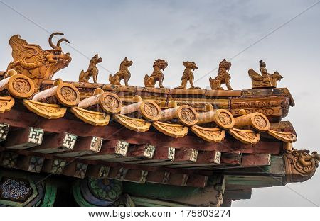 Beijing, China - Oct 30, 2016: Mythical beasts on roof gable of a palace building in the Forbidden City (Gu Gong, Palace Museum). Also called roof charms, roof figures or walking beasts.
