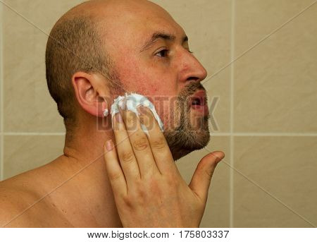 Portrait of a good looking young man putting shaving cream on his face and ready to shave his beard in the bathroom bald