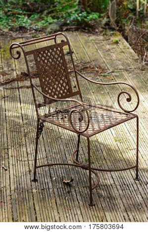 Rusty abandoned chair on neglected wooden decking in an overgrown poorly maintained garden