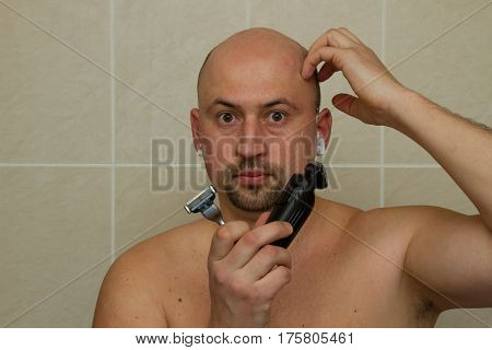 concept. The young man chooses what he shave electric razor or hand razor. Bald