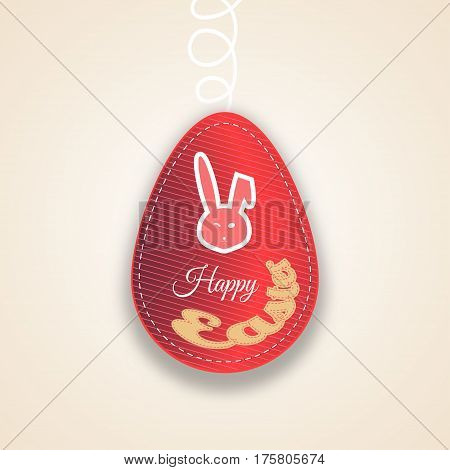 Vector paper label of Easter red egg with line pattern stitching rabbit head silhouette and yellow text cut from paper on the gradient light brown background.