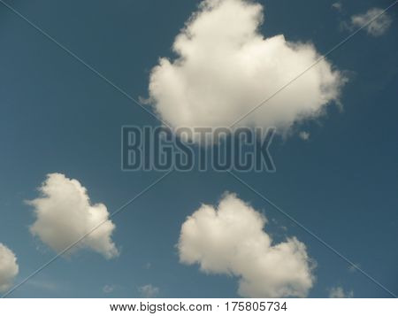 A trio of fluffy white clouds are pearl-like and float in a rich blue sky