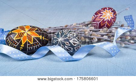 Hand painted eggs in ethnic style lovely polka dot ribbon willow twigs on blue fabric tablecloth. Soft light Easter background. Close shot. Ratio 16:9