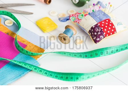 tool kit for cutting, sewing and production of scrappy blankets, quilt. Handmade pin cushion in style patchwork with multicolored sewing pins, tape-line lying, buttons, the color cut fabric and threads on a white background.