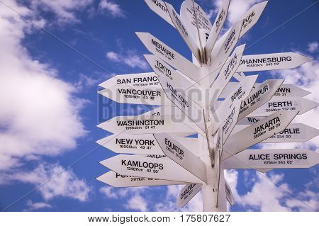International white sign posts with cloudy blue sky in background. Distances from Mt Isa in Outback Australia