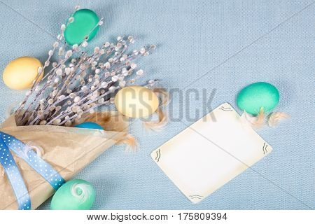 Paper package with willow painted eggs and feather on blue fabric tablecloth. Vintage card with space for your text. Soft light Easter background. Pastel shades. Top view.