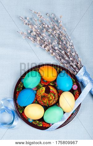 Hand painted wooden plate with colorful eggs willow with lovely polka dot ribbon on blue fabric tablecloth. Easter background. Ukrainian national painting petrikovka. Vertical orientation.