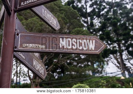 Wooden sign in Southeast Asia pointing towards Moscow, Russia