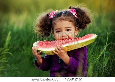 Happy child eating watermelon. Girl having picnic in autumn park