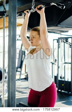 Young beginner girl exercising in the fitness gym, with lat machine
