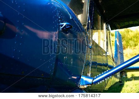 Blue Airpane Parked On The Grass At The Airfield