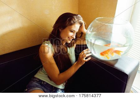 pretty woman playing with goldfish at home, sunlight morning happy lifestyle