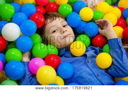 Young boy having fun playing with colorful plastic balls.