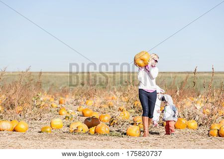 Cute kids in Halloween costumes at the pumpkin patch.