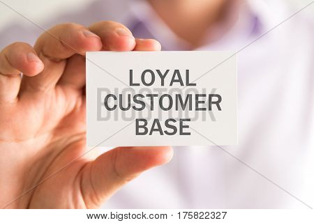Businessman Holding A Card With Loyal Customer Base Message