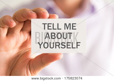 Businessman Holding A Card With Tell Me About Yourself Message