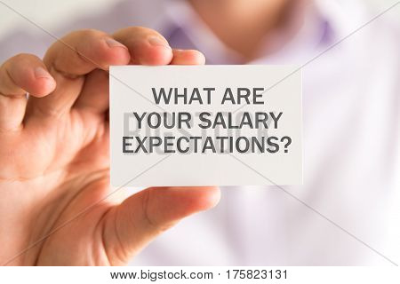 Businessman Holding A Card With What Are Your Salary Expectations Message