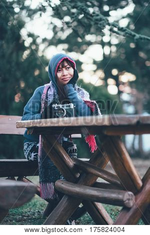 Girl in a winter coat out side sitting on the bench with camera on the table.