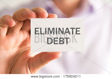 Businessman Holding A Card With Eliminate Debt Message