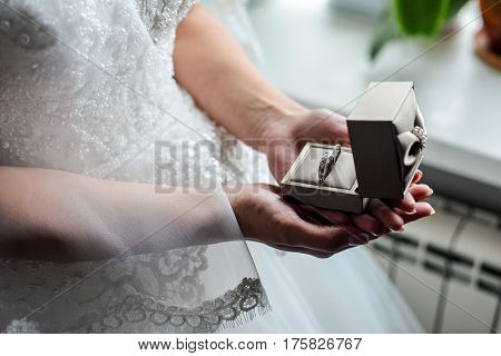 Engagement ring box in bride hands. Closeup of woman palms holding jewellery. Love, Wedding, Proposing, Marriage concept. Rustic chic style