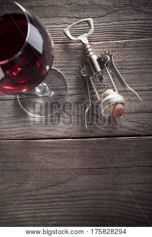 Corkscrew and a glass of wine on an old wooden table