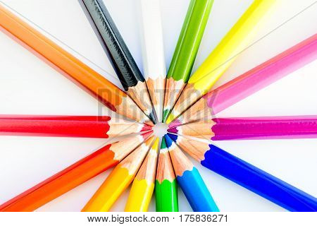 Close up macro shot of sharp colorful pencils pointed to each other ib a circle