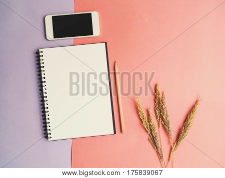 Top view of open notebook with pencil and mobile phone on colorful purple orange background