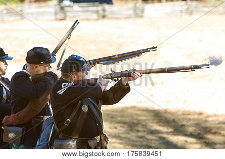 KENNESAW, GA - NOVEMBER 2016:  A small group of Civil War reenactors wearing union uniforms fire their muskets in a firing demonstration put on at Kennesaw Mountain National Battlefield Park in Kennesaw GA on November 20 2016.
