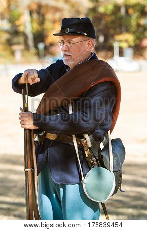 KENNESAW, GA - NOVEMBER 2016:  A Civil War reenactor wearing a union uniform demonstrates how to load a musket at a firing demonstration put on at Kennesaw Mountain National Battlefield Park in Kennesaw GA on November 20 2016.
