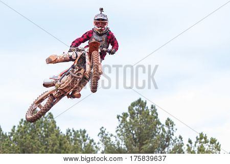 MONROE, GA - DECEMBER 2016:  A rider poses in midair after going over a jump in a motocross race at the Scrubndirt Track in Monroe GA on December 3 2016.