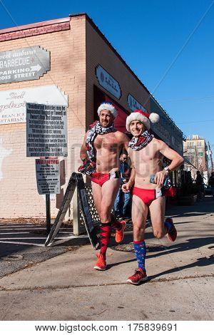 ATLANTA, GA - DECEMBER 2016:  Two male runners wearing speedo swimsuits jog down a city street at the Santa Speedo Run an annual charity fundraiser in Atlanta GA on December 10 2016.