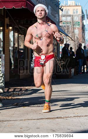 ATLANTA, GA - DECEMBER 2016: A male runner wearing Christmas lights a Santa hat and a skimpy swimsuit jogs down a city street at the Santa Speedo Run an annual charity fundraiser in Atlanta GA on December 10 2016.