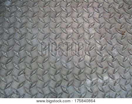 A gray steel plate with weld-marks on it to prevent slipping,
