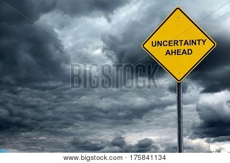 road warning sign with text uncertain ahead in front of storm cloud background