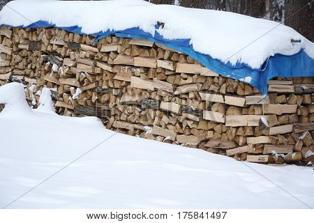 firewood stacking in the back yard covered from snow in winter