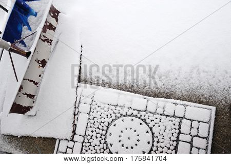 doormat and snow removal shovels in front door after snow