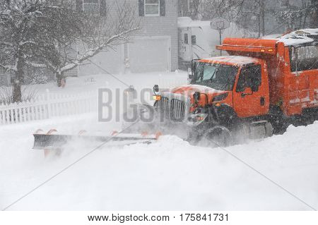 snowplow truck removing snow on the street after blizzard
