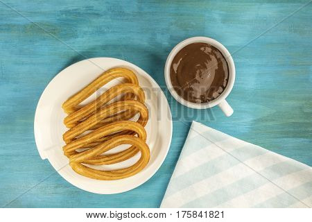 A photo of churros, traditional Spanish, especially Madrid, dessert, in the form of horseshoe, with a cup of chocolate on a wooden board texture, retro style, with copy space