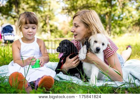 Mom and daughter with labrador puppy. mom and daughter posing with their pet and best friend outdoors