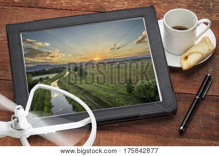sunset over Rocky Mountains and foothills with irrigation ditch, aerial photography concept - reviewing pictures on digital tablet with a drone and coffee, screen picture copyright by the photographer