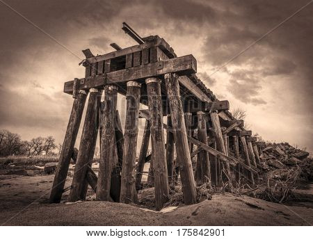 railroad timber trestle destroyed by river flooding - St Vrain Creek near Platteville, Colorado, sepia toning