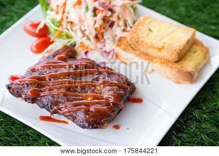Close up view of pork barbecue ribs with barbecue sauce that served with garlic bread and vegetable salad.