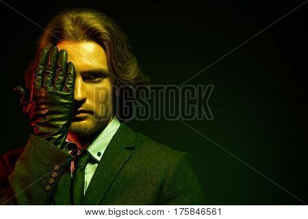 Respectable well-groomed man in an expensive suit and black leather gloves. Male beauty, fashion. Accessories.