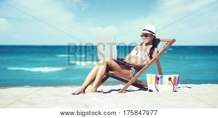 Young, beautiful, sporty and sexy woman with laptop relaxing on the beach. Traveling, vacation, concept.