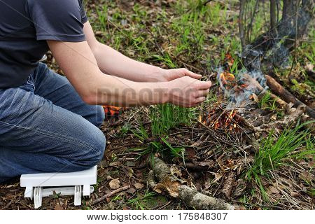 The man in the woods. The man sitting on his knees in the forest among the dry withered leaves. People kindle fire.