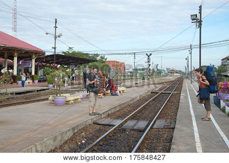 AYUTTHAYA, THAILAND - JANUARY 02, 2017: A young family of tourists-backpackers in the train station of Ayutthaya sity