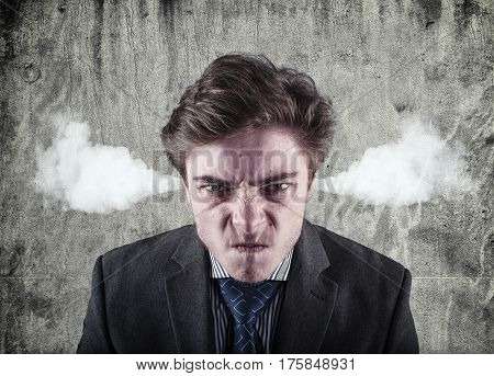 Angry young man blowing steam coming out of ears about to have nervous atomic breakdown. Negative human emotions facial expressions feelings attitude