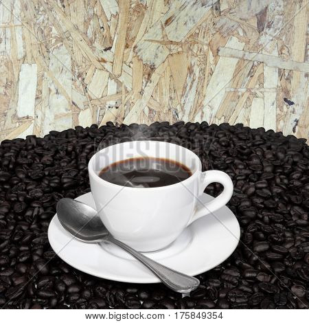 Black coffee in cup and coffee beans with smoke on old wood board background.