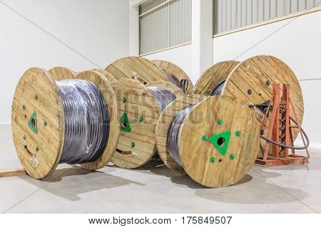 Wooden reel of power conductor cable in the distribution warehouse of factory plant